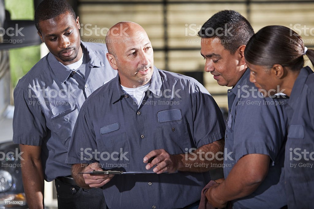 Team of mechanics looking at clipboard stock photo