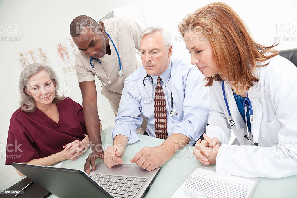 Team of Medical Personnel Looking at Computer Records Together royalty-free stock photo