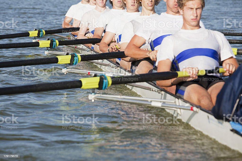 Team of men oaring canoe stock photo