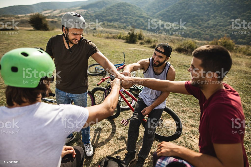 Team of mountain bike riders fist bumping in nature. stock photo