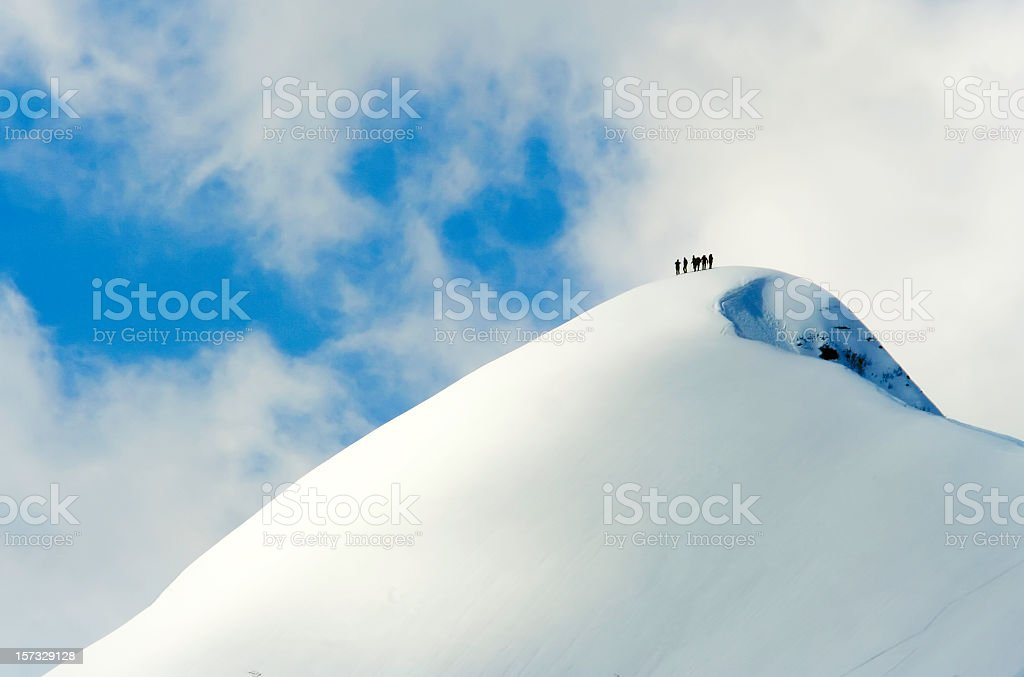 A team of people climbing a snowy mountain royalty-free stock photo