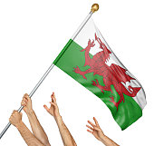 Team of peoples hands raising the Wales national flag