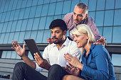 Team of shocked business people using digital tablet outdoors.