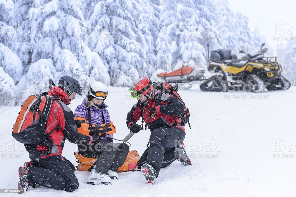 A team of ski patrols aiding a woman who fell stock photo