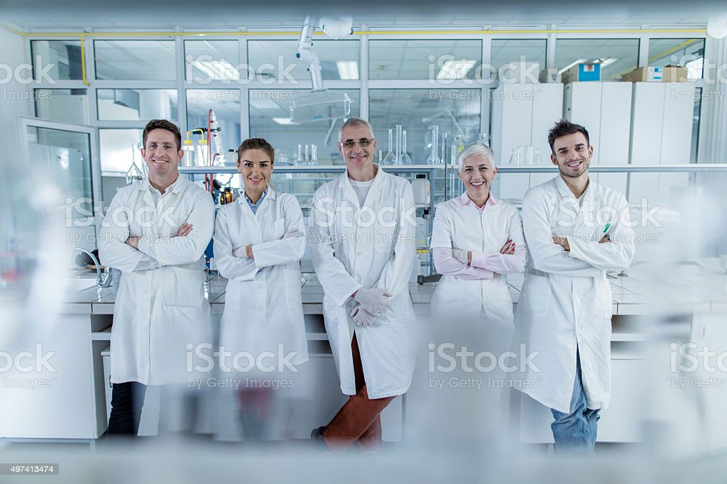 Team of smiling chemists with crossed arms in a laboratory. stock photo