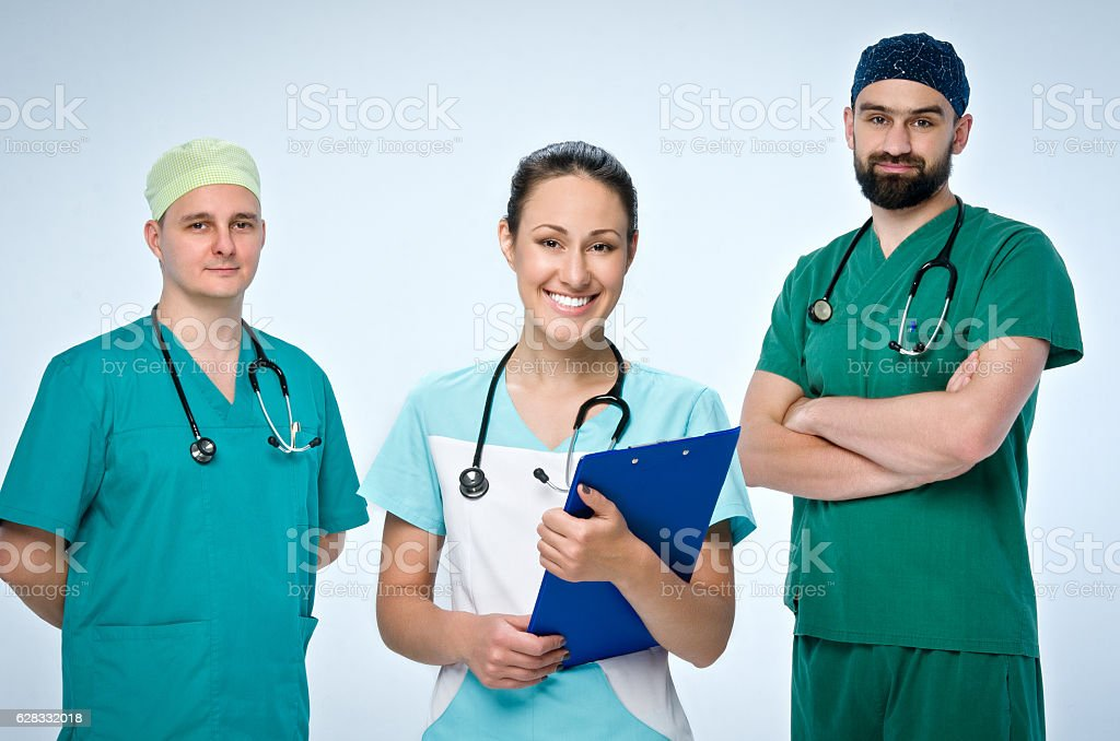 Team of three young doctors in green scrubs. stock photo