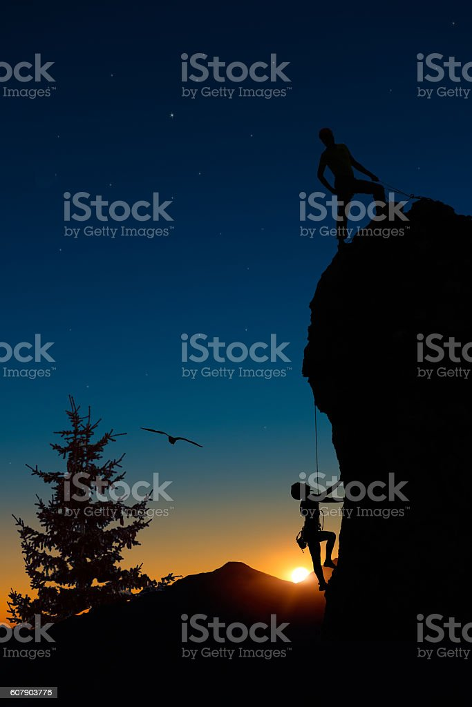 Team of two mountaineers roped climb the mountain. stock photo