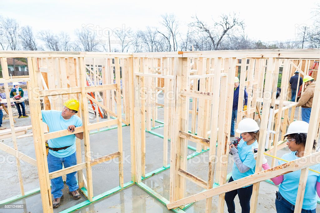 Team of volunteers build charity home stock photo