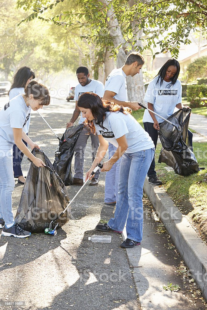 Team Of Volunteers Picking Up Litter In Street stock photo