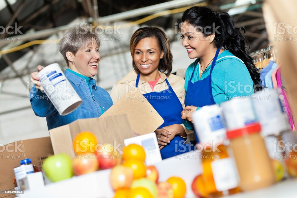 Team of volunteers working with donated food at donation center royalty-free stock photo