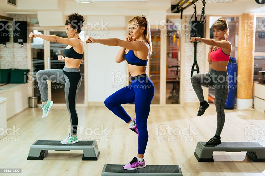 Team of women exercising step aerobics at the gym. Side view.