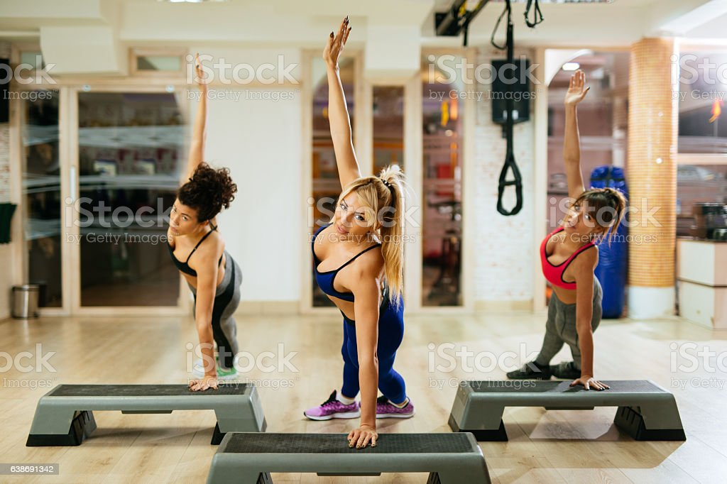 Team of women exercising step aerobics at the gym. stock photo