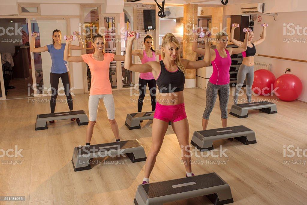 Team of women having step aerobics in a health club. stock photo