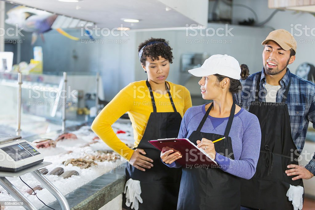 Team of workers in seafood market stock photo