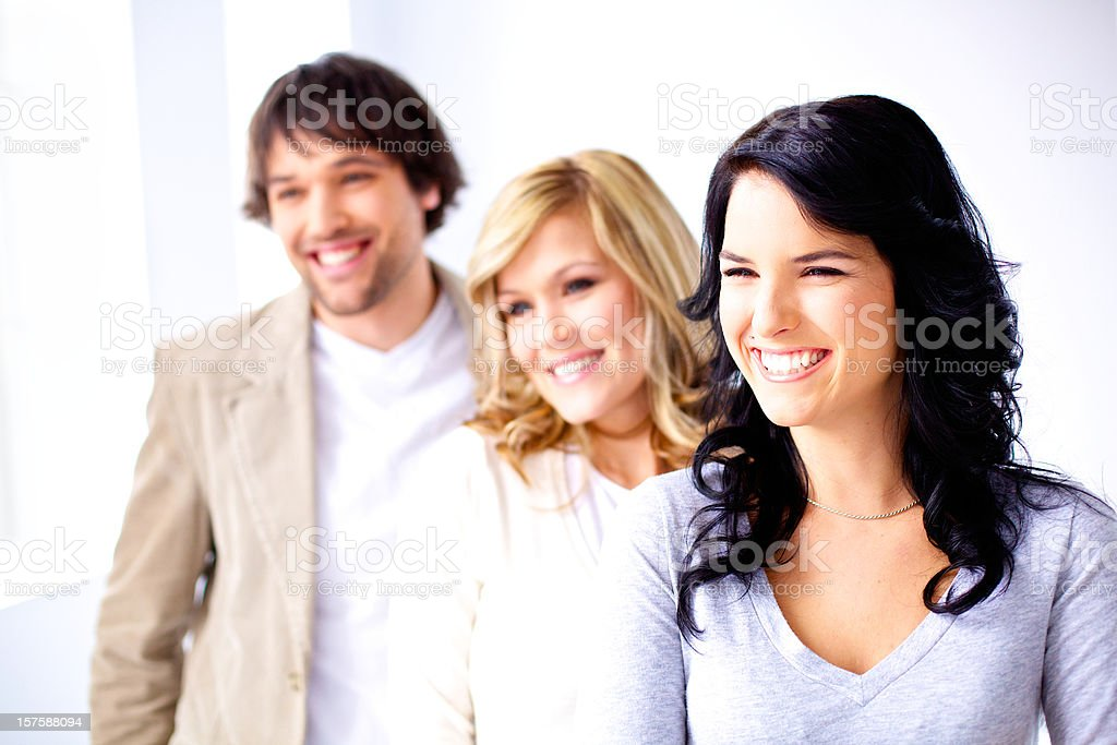 team of young adult smiling and looking away royalty-free stock photo