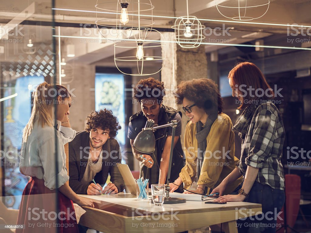 Team of young designers having a meeting in the office. stock photo