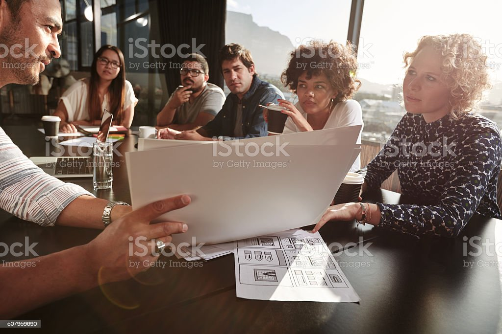 Team of young people going over paperwork stock photo