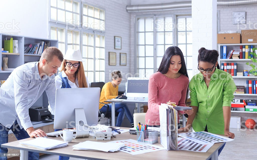Team of young people working at workplace stock photo