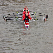 Team of young women rowing to a race start point