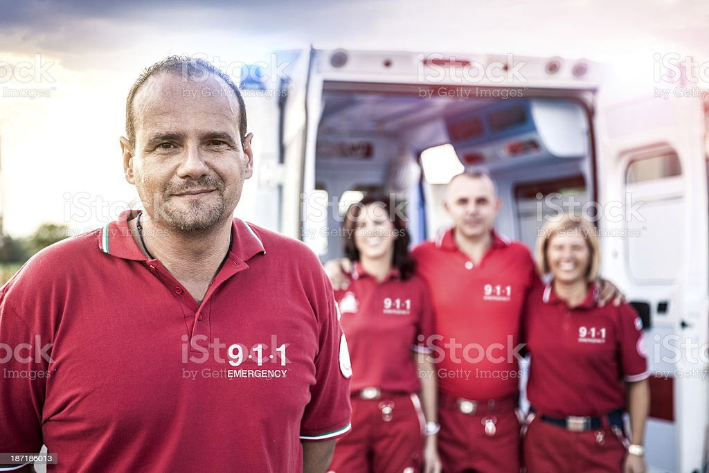 EMT team posing in front of an ambulance stock photo