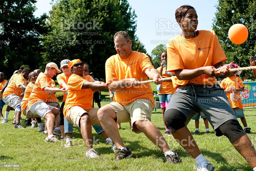 Team Pulls Rope In Adult Tug-Of-War Competition stock photo