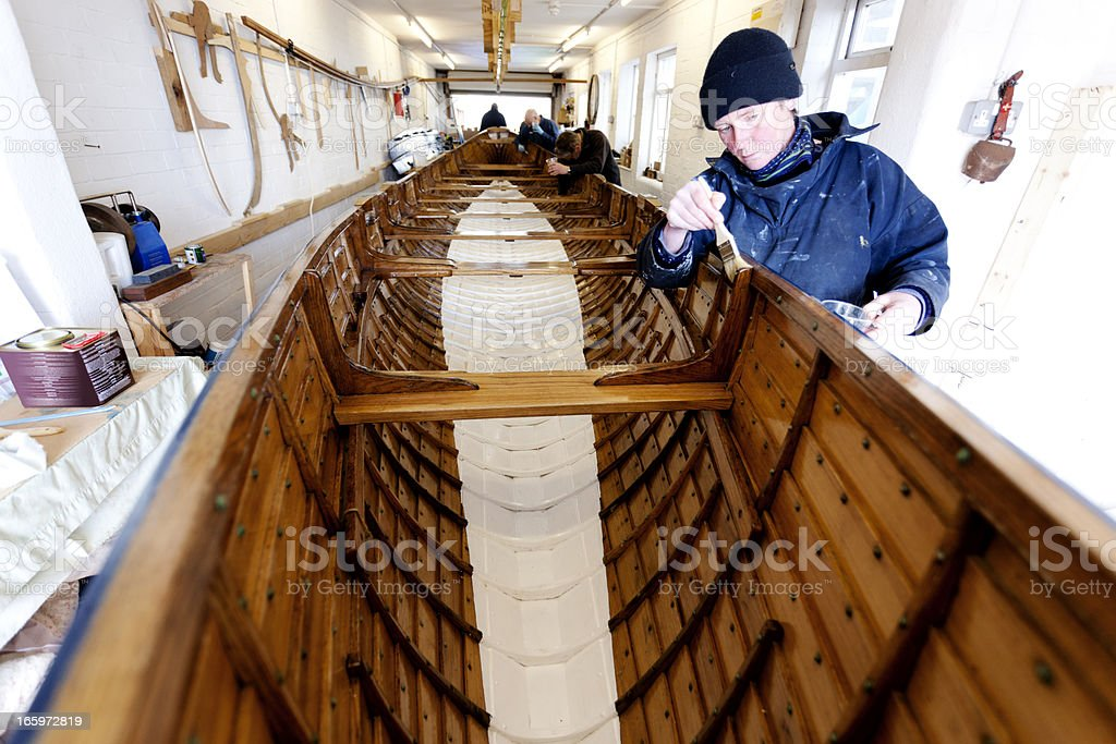 Team varnishing a gig boat royalty-free stock photo
