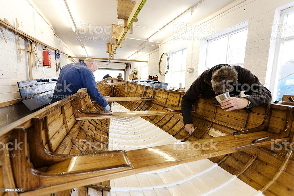 Team varnishing a gig boat stock photo