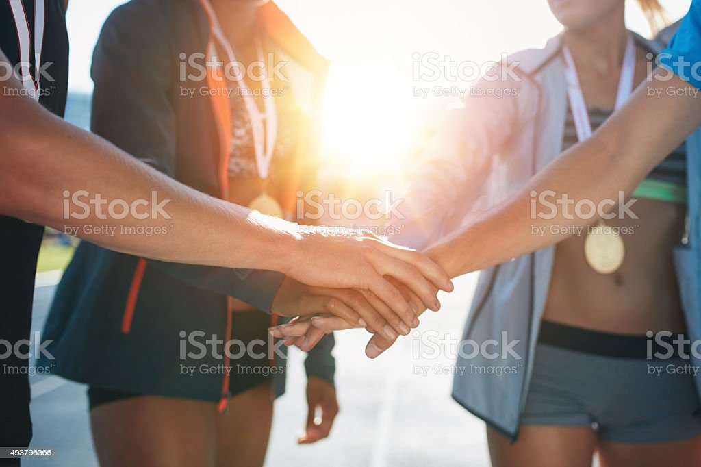 Team with hands together celebrating success stock photo