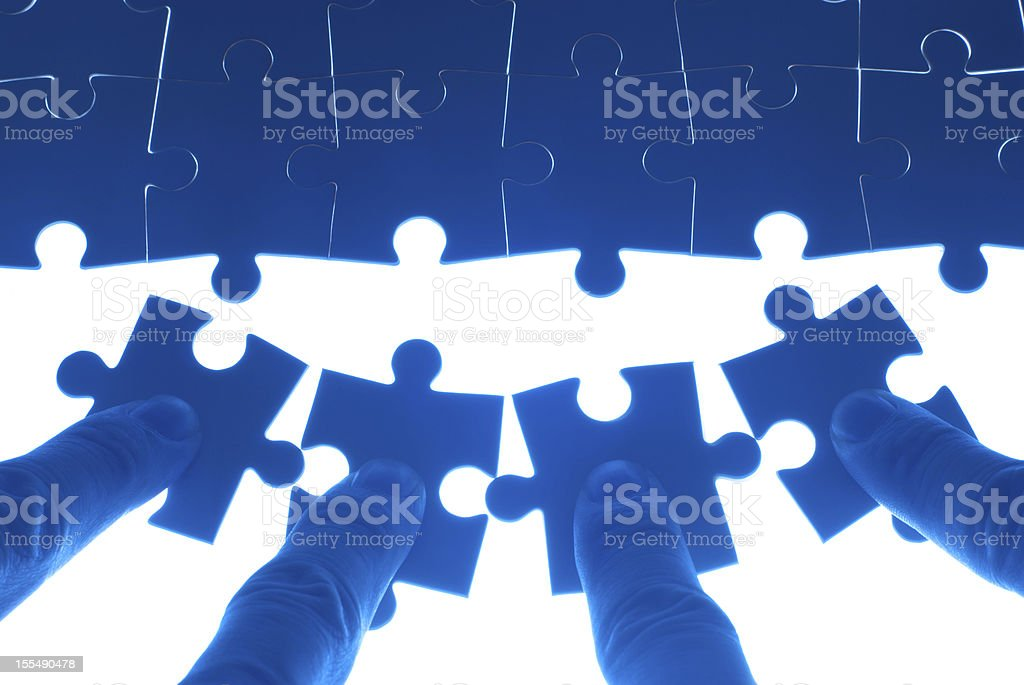 Team work on solving puzzle problem royalty-free stock photo