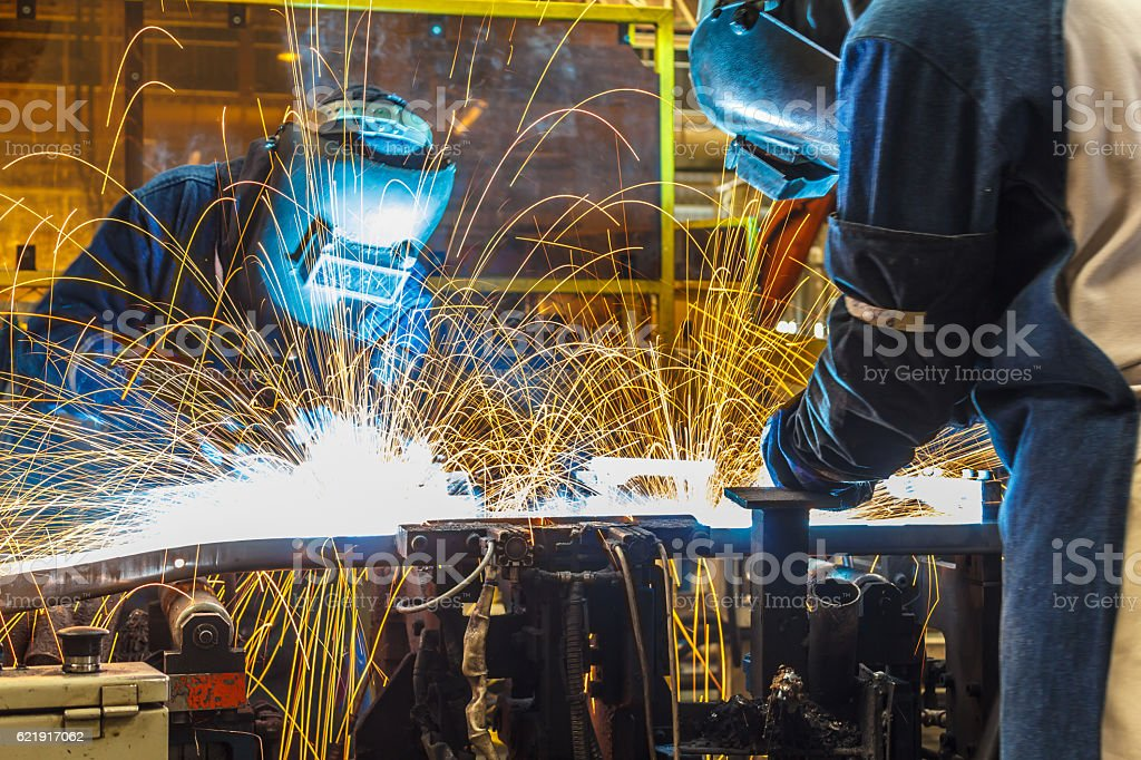 Team worker with protective mask welding. stock photo