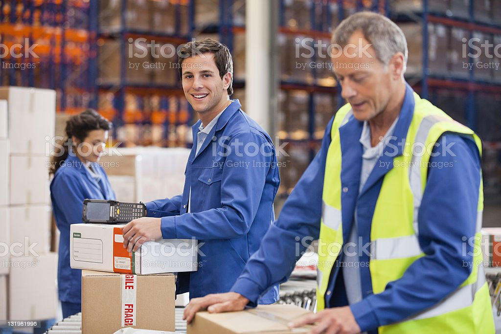 Team working at warehouse with cardboard stock photo