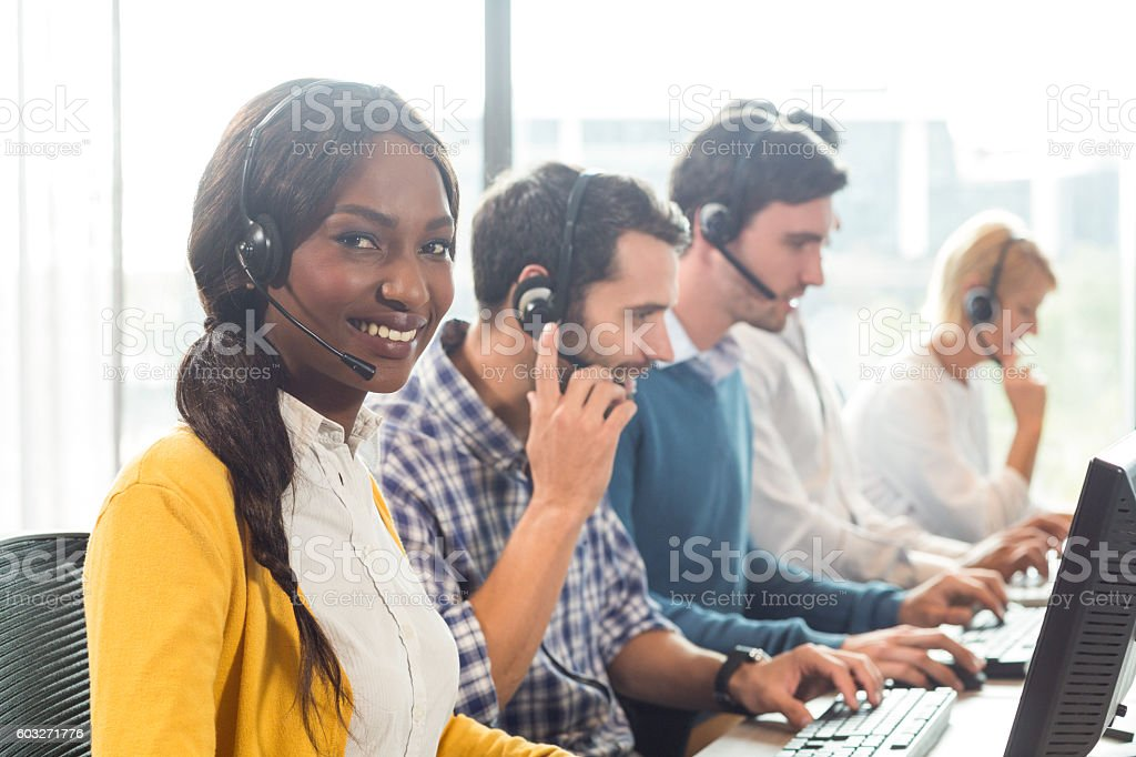 Team working on computer with headset stock photo