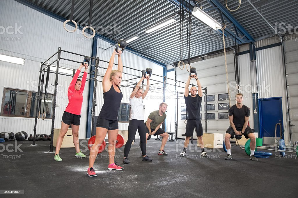 Team workout with kettlebells at fitness gym stock photo