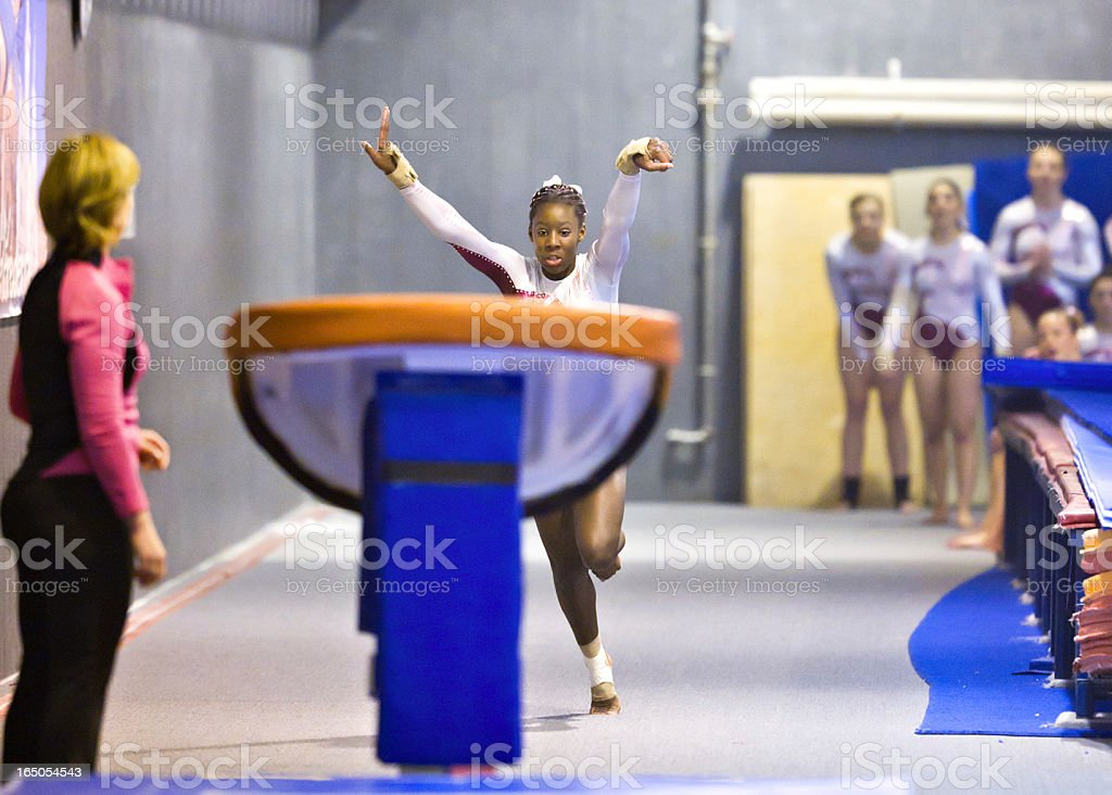 Teammates and Coach Watch Gymnast Performing Vault stock photo