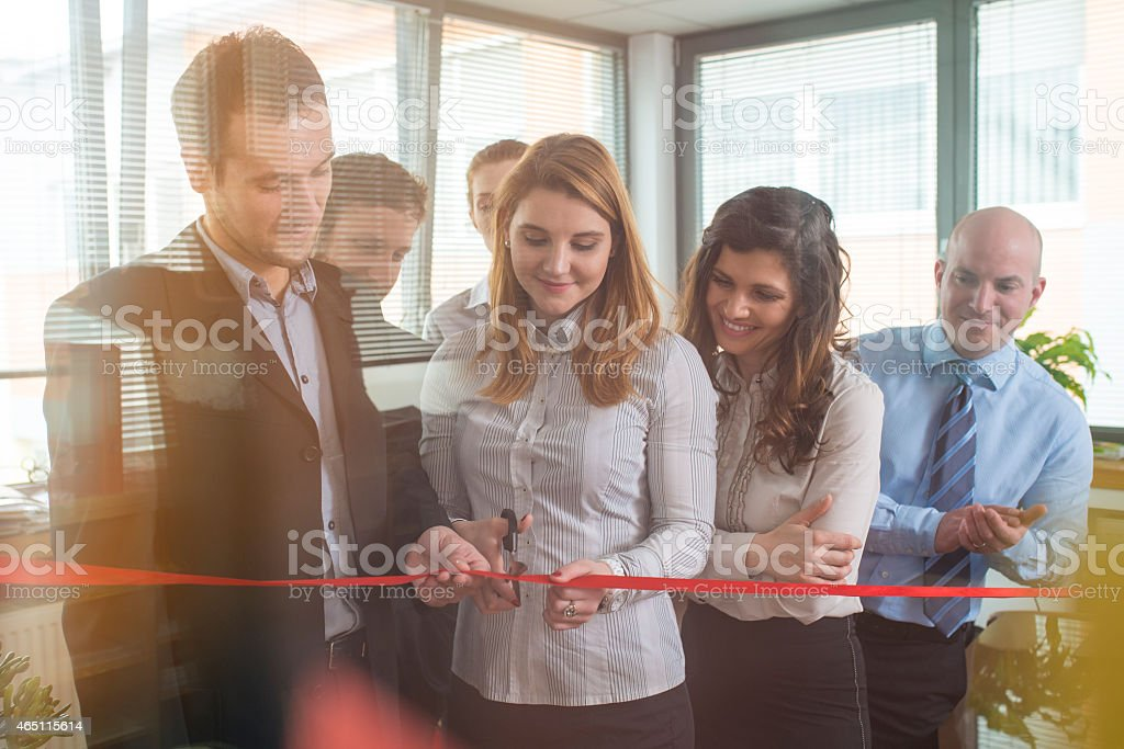 Teammates at an office cutting a ribbon for a new beginning stock photo