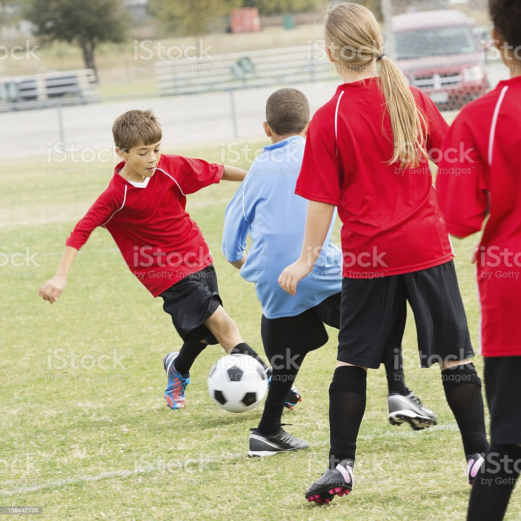 Teams of children playing in outdoor soccer game royalty-free stock photo