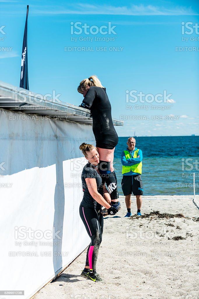 Teamwork as two women climbs wall in obstacle course run stock photo