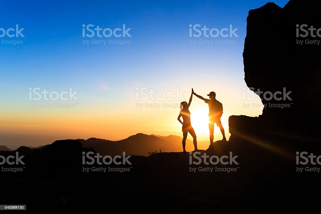 Teamwork couple climbing helping hand stock photo