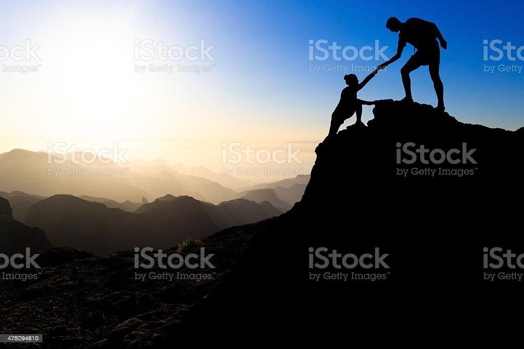 Teamwork couple hiking helping hand stock photo