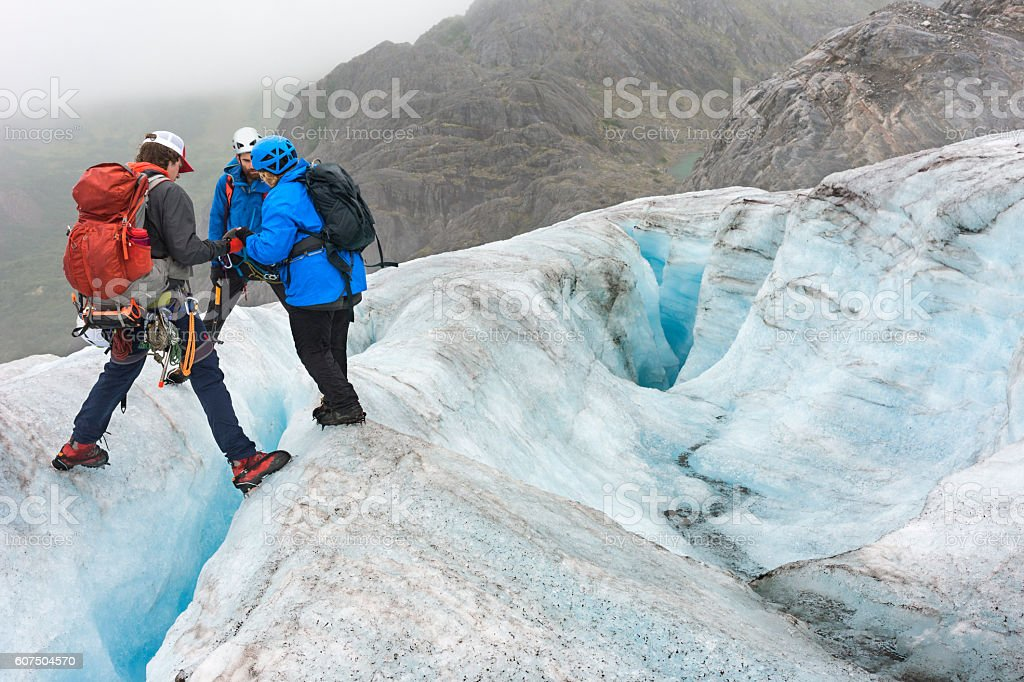 Teamwork crossing crevasses stock photo