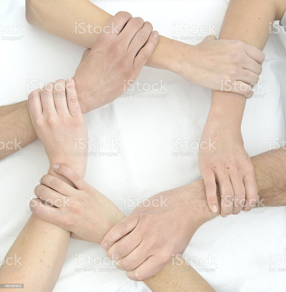 Teamwork hands with grip on each other in circle touching stock photo