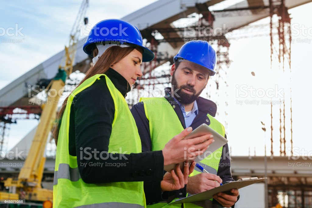Teamwork in construction industry - two engineers working together on construction site with blueprints and plans stock photo