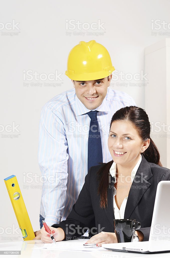 Teamwork in modern office with engineer with helmet and businesswoman royalty-free stock photo