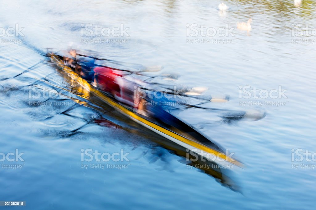 Teamwork, motion blurred rowers in rowing boat training on river stock photo