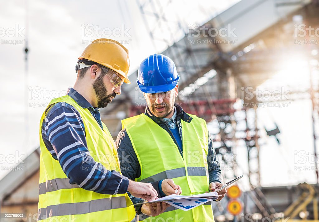 Teamwork on construction site with two engineers stock photo