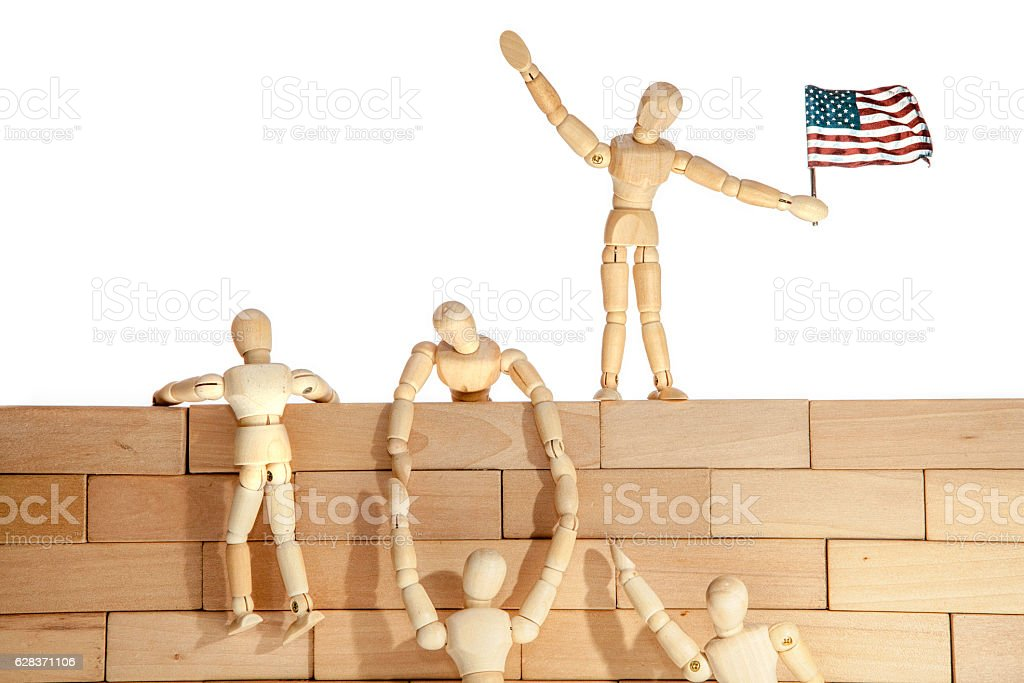 Teamwork or Illegal immigrants climbing a USA border wall stock photo