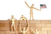 Teamwork or Illegal immigrants climbing a USA border wall