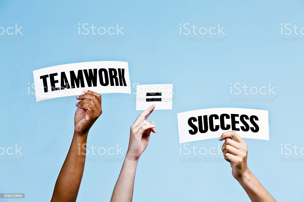 'Teamwork = Success' say hand-held signs against pale blue stock photo