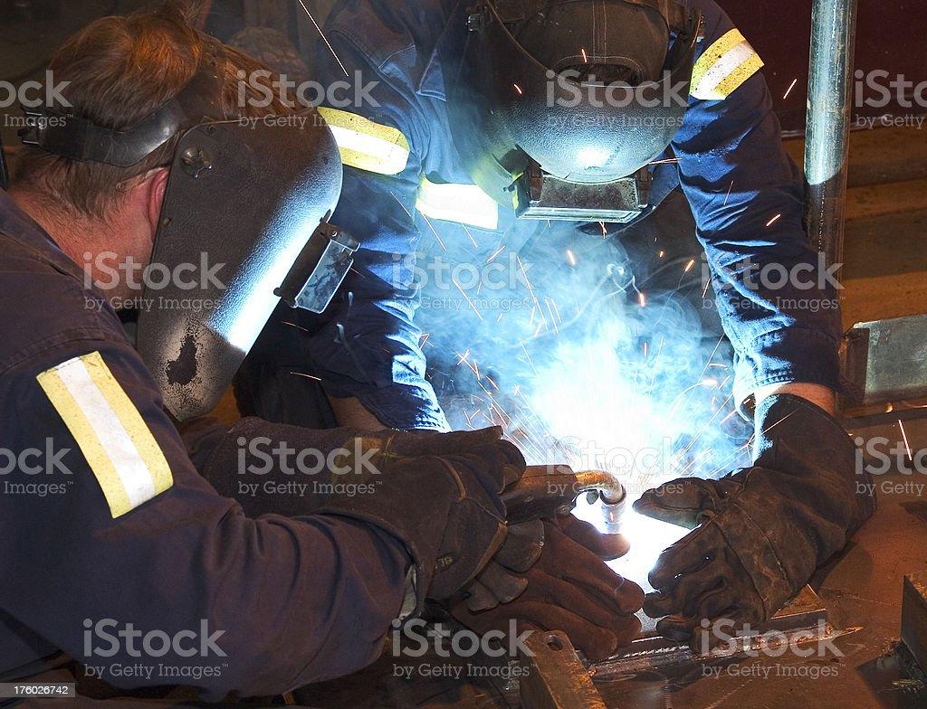 Teamwork: two men welding metal royalty-free stock photo