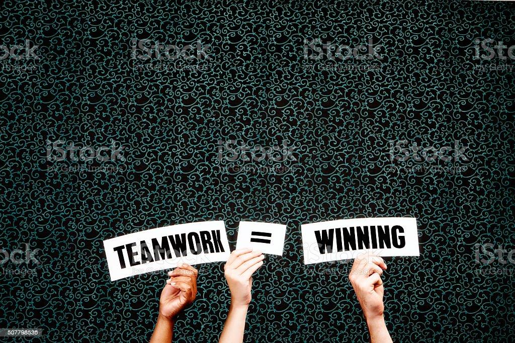 'Teamwork = winning' say hand-held words on dark background stock photo